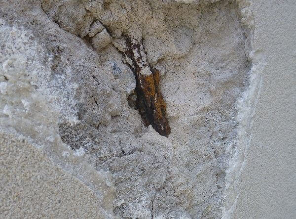 Figure 2. Spalled concrete on a hotel wall exposes corroded reinforcing rods.