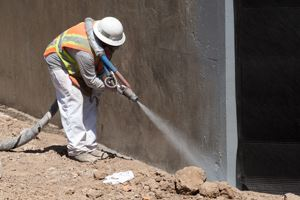 Worker spraying a polyurea coating.
