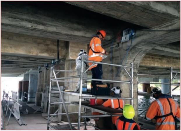 workers repairing concrete bridge