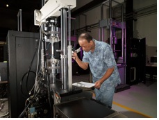 Figure 1. A technician monitoring fatigue crack growth testing with a hydraulic fatigue tester.