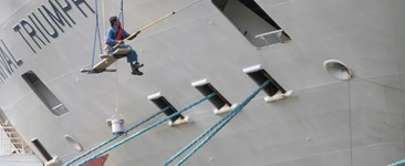 worker painting a marine ship with a coating