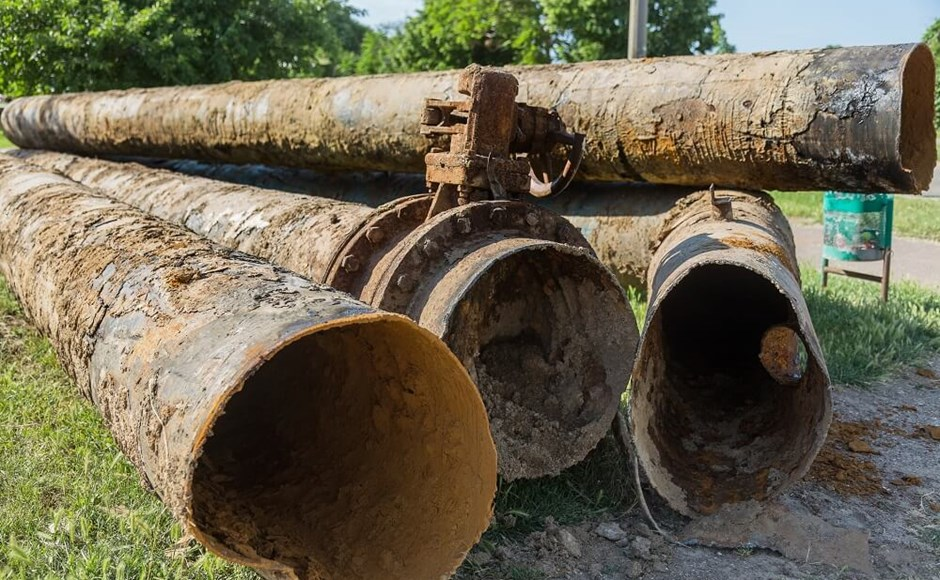 Old large rusty water pipes. Corroded metal pipe destroyed.