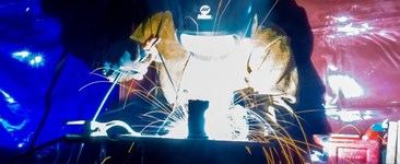 Welding with stick electrode with sparks flying - on a red and blue background.