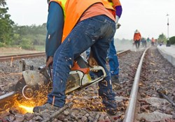 Worker performing maintenance on railway railroad track.