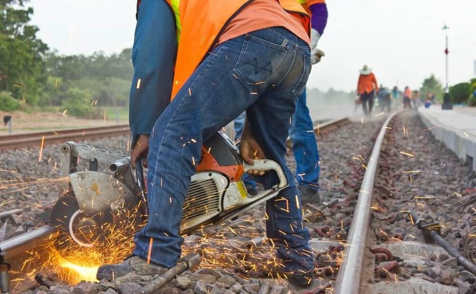 Worker performing maintenance on railway railroad track.
