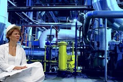 Corrosion engineer among equipment and pipes holding a blueprint and checklist