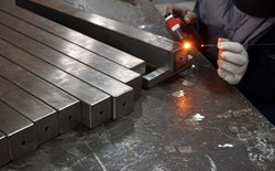 A worker welding stainless steel beams.