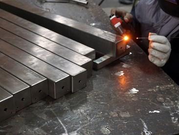 A worker welding stainless steel beams.