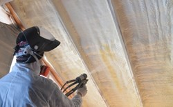 Technician spraying a metal structure with polyurea.