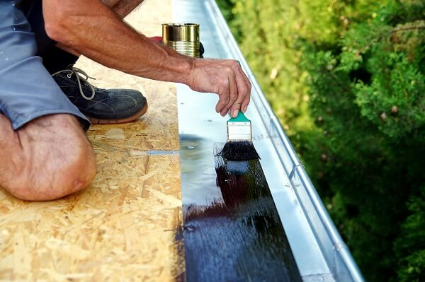 Figure 1. Worker applying a polymer modified bitumen waterproof coating to a rooftop.